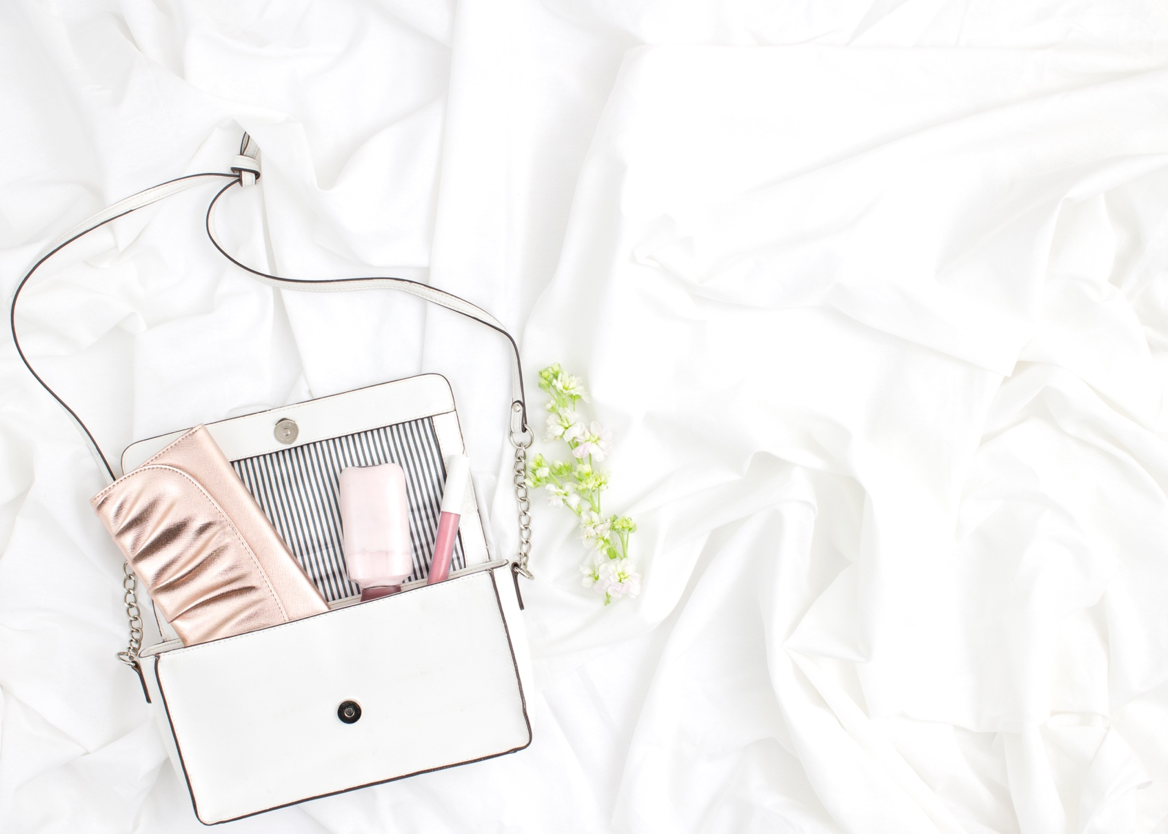 white flat lay with flowers and purse